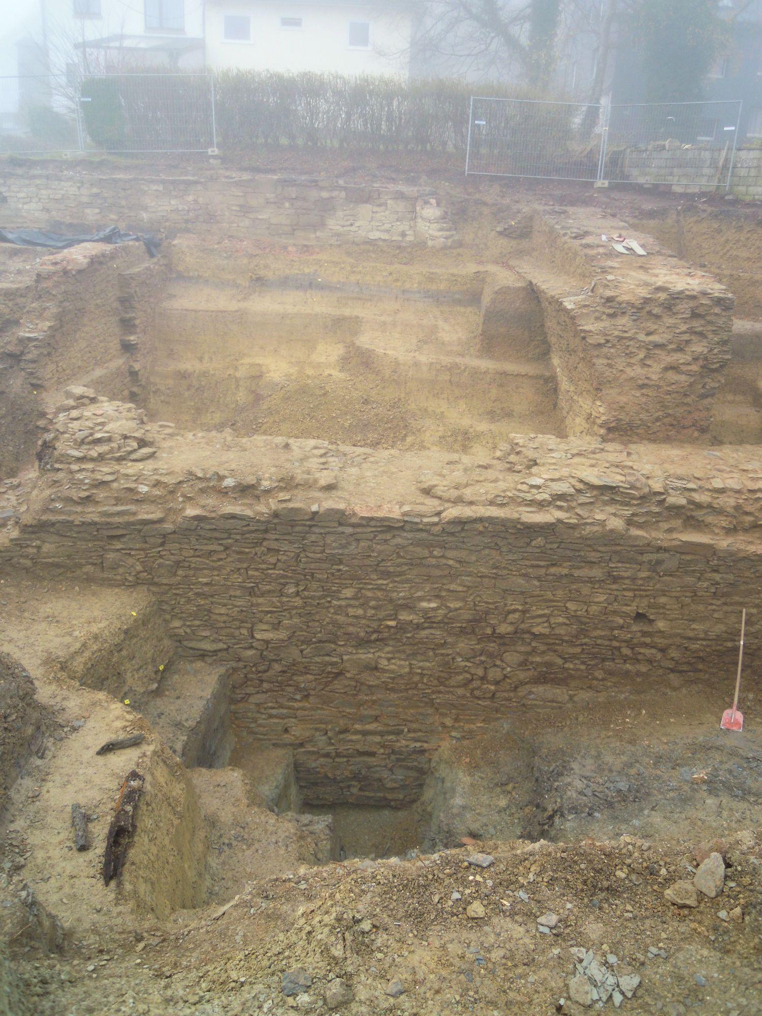 10.11.2020: Die 4 m hohe Mauer (im Vordergrund) wurde bis zum Fundament freigelegt. Die graue Färbung des Bodens (rechts) sind Überreste eines Wassergrabens.